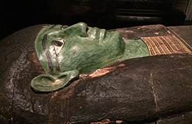 The malachite-painted face on wooden coffin